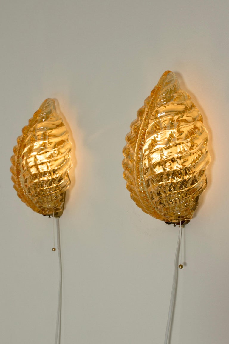 Pair of beautiful Swedish modern wall lamps from Orrefors. Made from glass in a warm amber color, in the form of leaves. Thick glass quality with a fluid look.