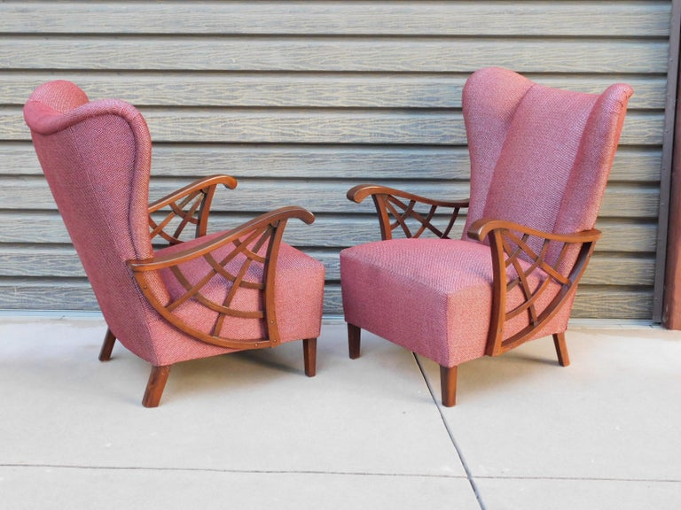 Pair of highly unusual Swedish winged back upholstered armchairs. Covered in burgundy and silver cotton/chenille. With spider web arm detail in stained elm. Completely restored and reupholstered by our craftsmen and ready for a life time of good use.