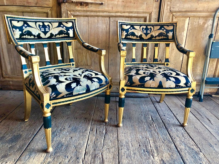 A pair of Swedish giltwood Armchairs in the neoclassical manner, late 18th/early 19th Century, with black painted accents, the back and seat upholstered in gold, cream and black silk needlepoint fabric (wear to front edge of fabric on one seat).