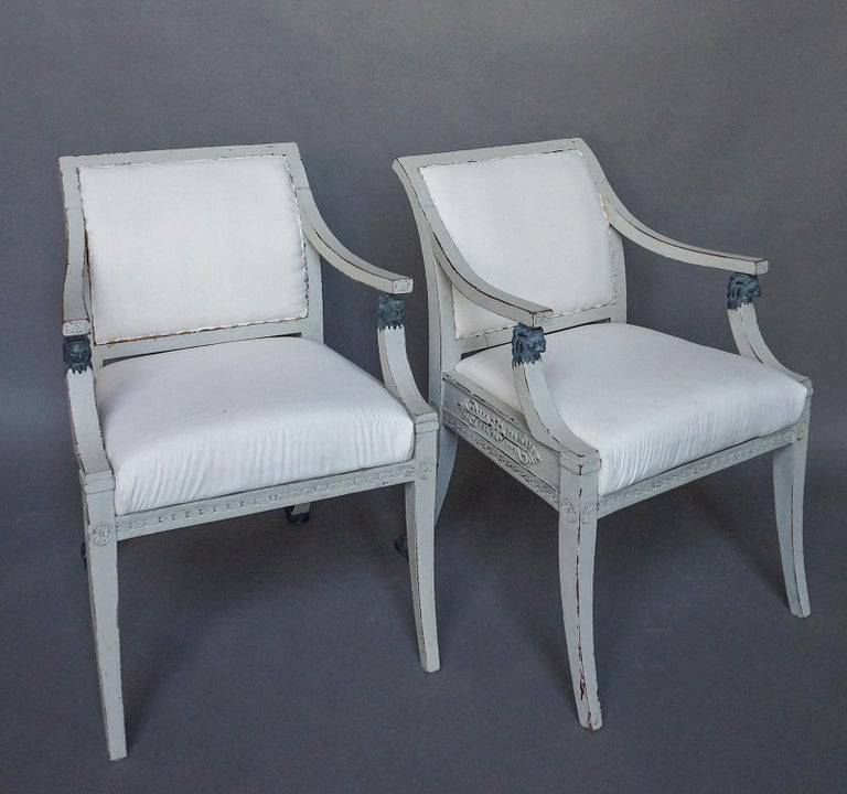 Pair of Swedish armchairs in the neoclassical style, circa 1900. The sides and backs of the frame have acanthus leaf carvings, and the arms are supported by lions' heads. The rear saber legs terminate in paw feet. Upholstered backs and slip seats.
