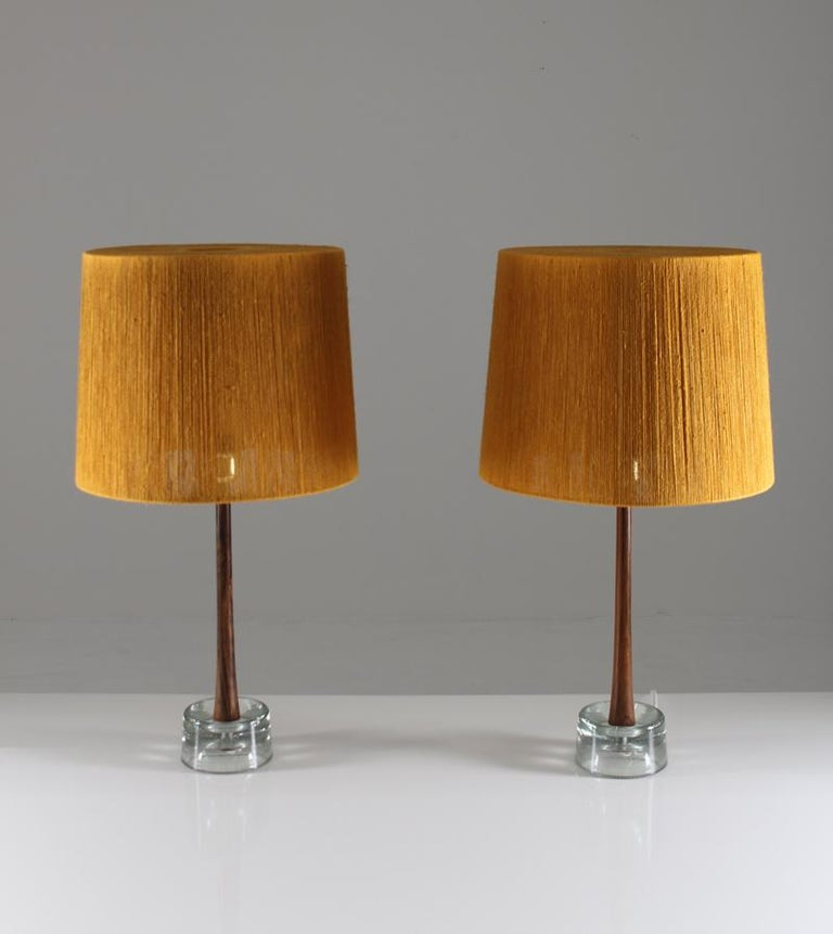 This rare set of two midcentury table lamps was manufactured in the 1960s by Stilarmatur Tranås in Sweden. The lamps consist of a clear glass foot, underneath a stem in beautiful rosewood. They come with gorgeous vintage shades in gold-yellow