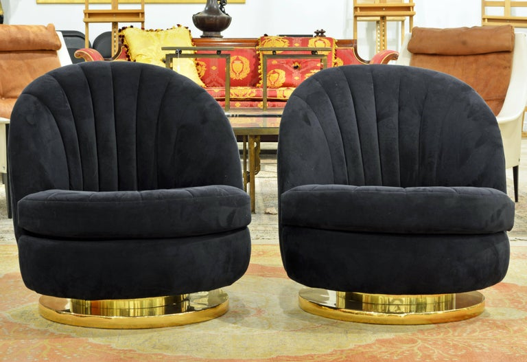 This attractive Mid-Century Modern pair of iconic lounge chairs are covered with blue micro suede in immaculate condition. Resting on a circular brass and chrome base the chairs turn 360 degrees and at the same time tilt to accommodate maximum