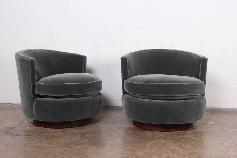 A pair of swivel chairs with walnut plinth bases. Designed by Edward Wormley for Dunbar. Fully restored and upholstered in mohair with down seat cushions.