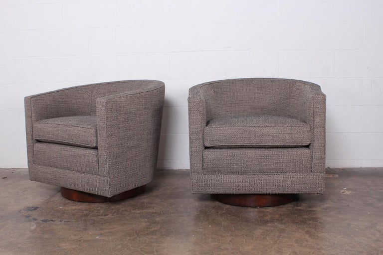 A pair of swivel chairs on walnut bases designed by Edward Wormley for Dunbar.