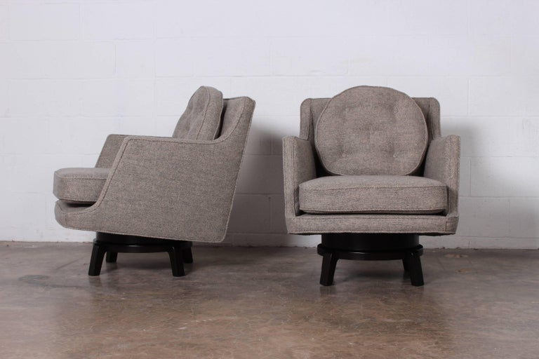 A pair of swiveling lounge chairs on mahogany bases. Designed by Edward Wormley for Dunbar.