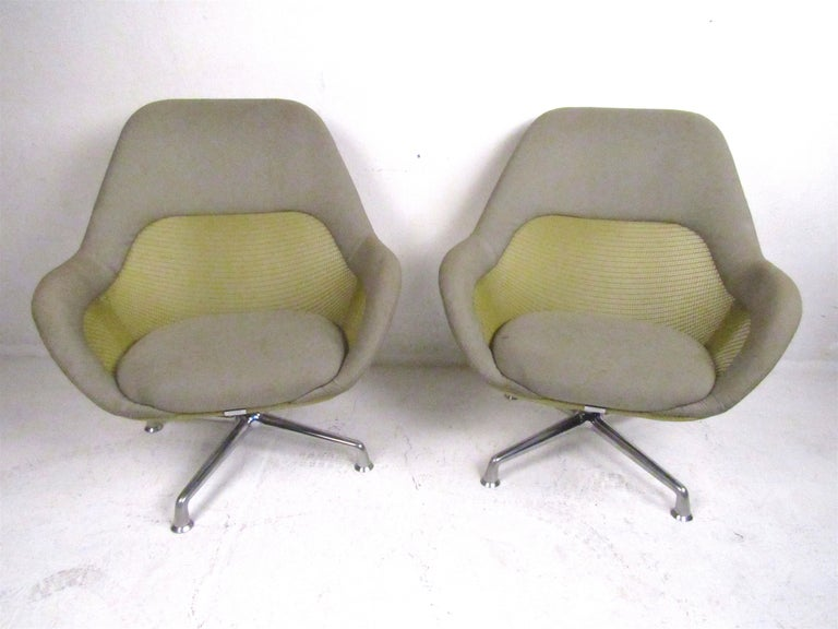 A set of modern Coalesse lounge/office chairs. A beautiful color combination of grey fabric, green mesh with solid metal legs. These chairs offer a very comfortable seating position as well as the ability to swivel making them a great addition to