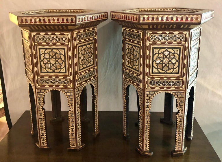 Pair of Syrian end tables or pedestals. This is a superb intricately inlaid pair of side tables decorated with mother of pearl from Damascus and dating from the mid-20th century. The octagonal shaped tables feature beautifully detailed inlaid mother