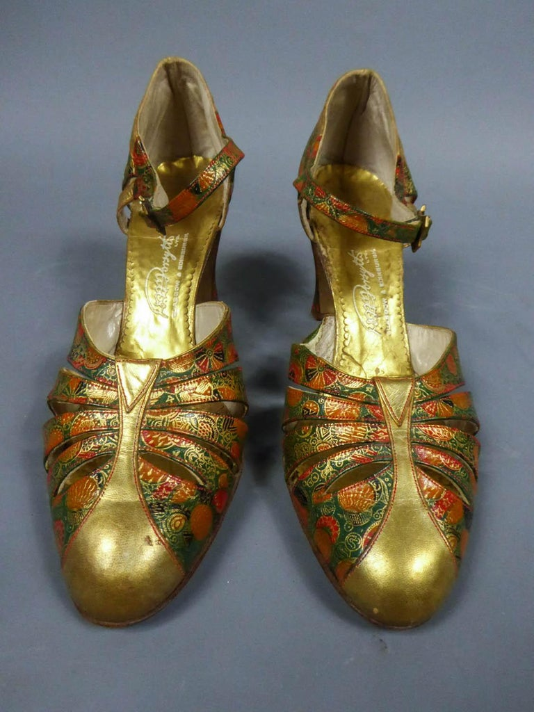 Circa 1930 Scotland  Heels or pair of T-bar shoes Salome for the ball dating from the Belle Epoque and Scottish origin. Printed and engraved leather with green, red, gold and black Art Deco pattern. Appliqués of golden leather. Gold and engraved