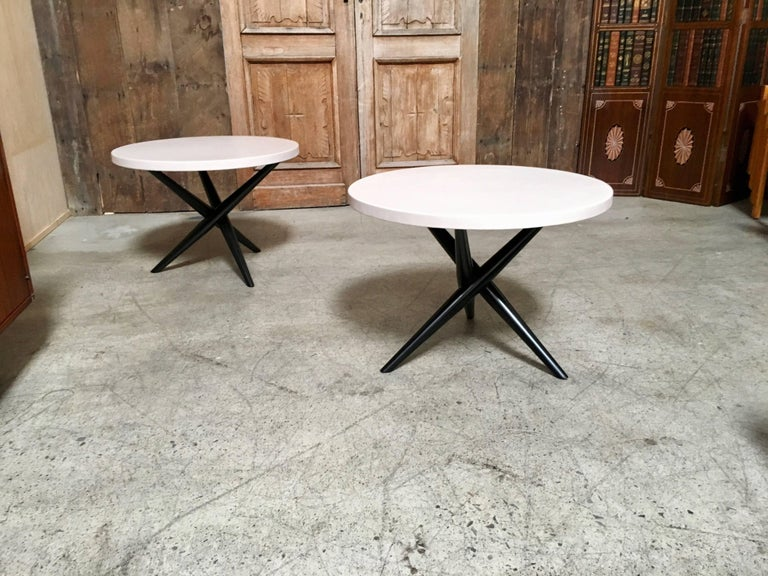 Pair of jax tables with ebonized base and creamy ivory leather top.