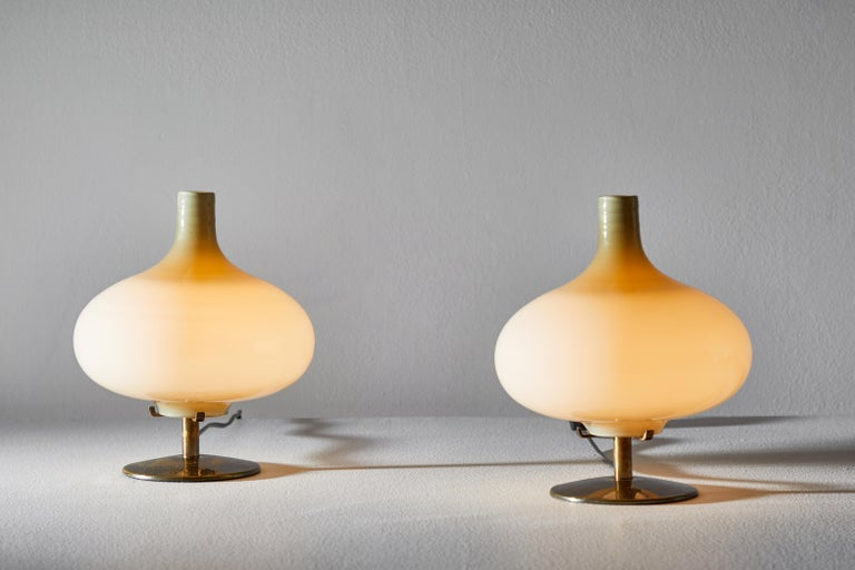 Pair of table lamps by Annig Sarian. Manufactured in Adrasteia, Italy, 1960. Brass, blown glass diffuser. Original cord. Each light takes one E27 European candelabra 60w maximum bulb. Bulbs provided as a one time courtesy. Literature: Bibliography