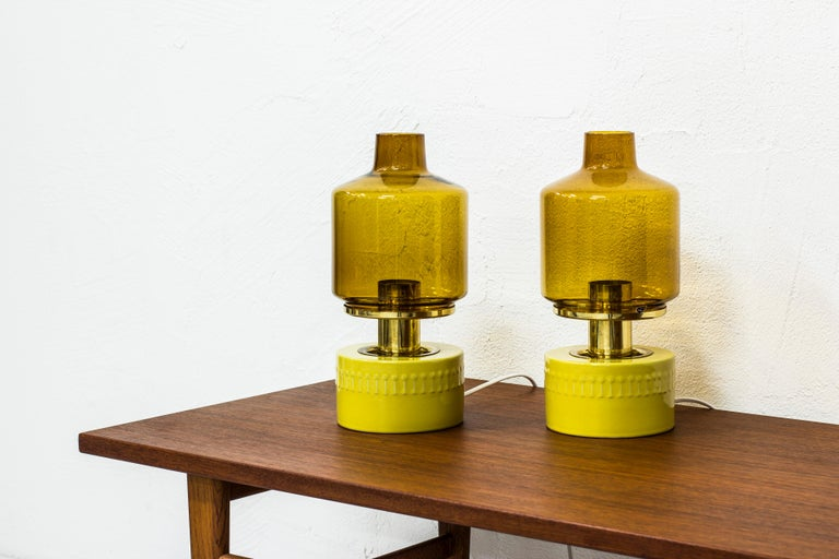 Rare pair of table lamps designed by Hans Agne Jakobsson. Produced by his own company in Markaryd. Made from brass, glass and stoneware. The ceramic part was made on commission by Höganäs Keramik. Light switch on the chord. Excellent vintage