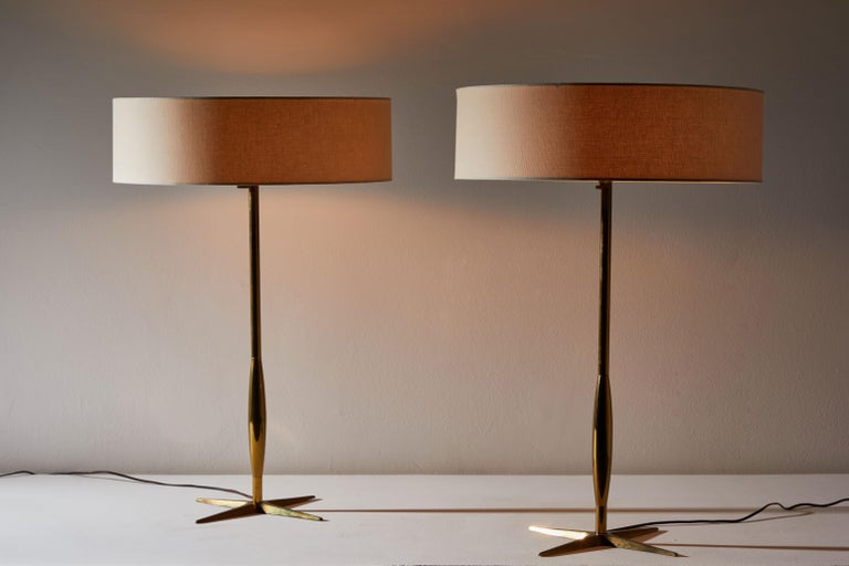 Pair of table lamps by Stiffel. Manufactured in the USA, circa 1950s. Brass base and stems. Custom linen shades. Original cords. Each light takes three E26 25W maximum bulbs.