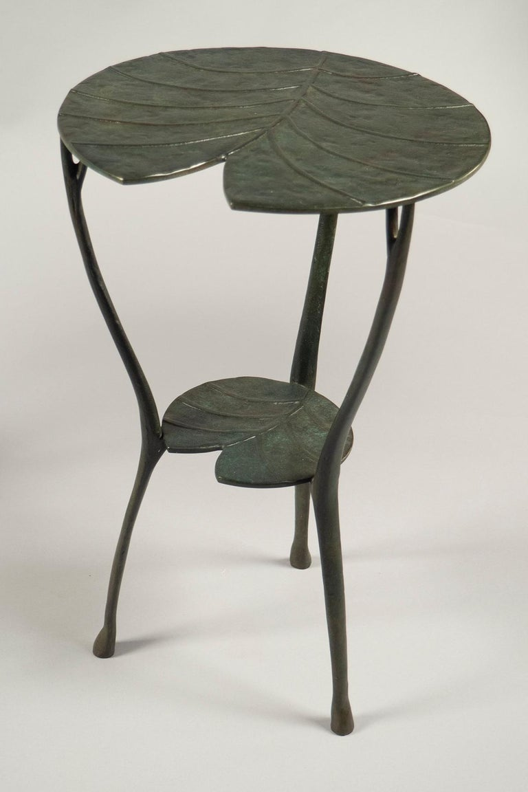 Cast bronze two-tier tables with their surfaces in the shape of water lilies, finished a dark green patina. Limited editions 3+4/99.