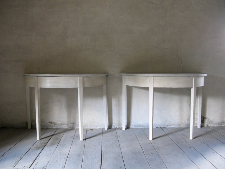 A lovely pair of painted wood demilune console tables from the early-19th century, with distressed finish, Gustavian style.  Born in the UK during the first quarter of the 19th century, each of this pair of demilune tables features a semi-circular