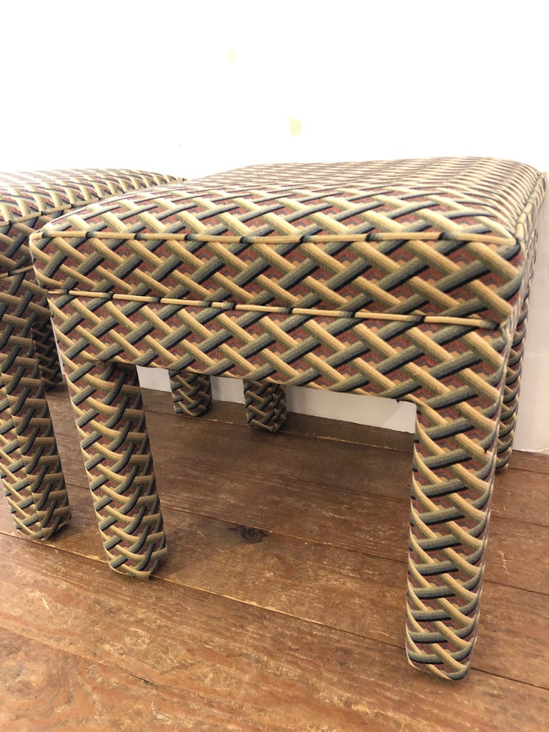 A pair of plush Parsons style Mid-Century Modern upholstered benches or ottomans in a handsome geometric pattern.