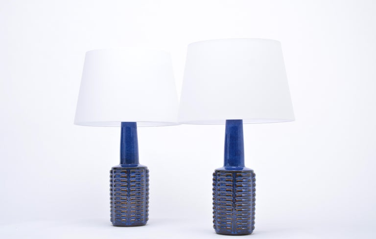 Pair of tall table lamps made of stoneware with ceramic glazing in different tones of blue. Graphic pattern to the base of the lamp. Designed by Einar Johansen and produced by Danish company Soholm. The lamps have been rewired for European use and