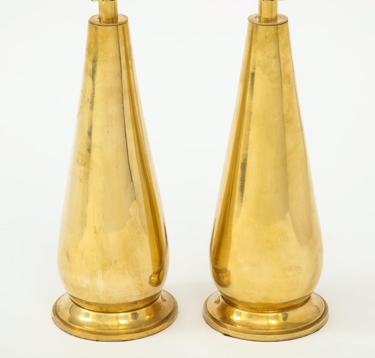 A stunning pair of brass lamps in a sleek teardrop shape on a brass base. Their vintage age gives them a lovely patina--a wonderful way to add a bit of shine and warmth to a room!