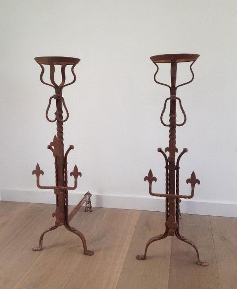 This tall pair of gothic style wrought iron andirons are also called landiers because of the shape of the top parts that where used to have water or soup boiling on receipt near the fire. They are rusty colored, have Fleurs de Lys decorations,