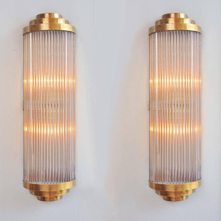 This 'Ravello' wall light takes its inspiration from a timelessly classic Art Deco design. Multiple Italian glass rods form a semi-circle which is capped, top and bottom by 3 tiers of curved brass. The brass back plate holds two light bulbs and