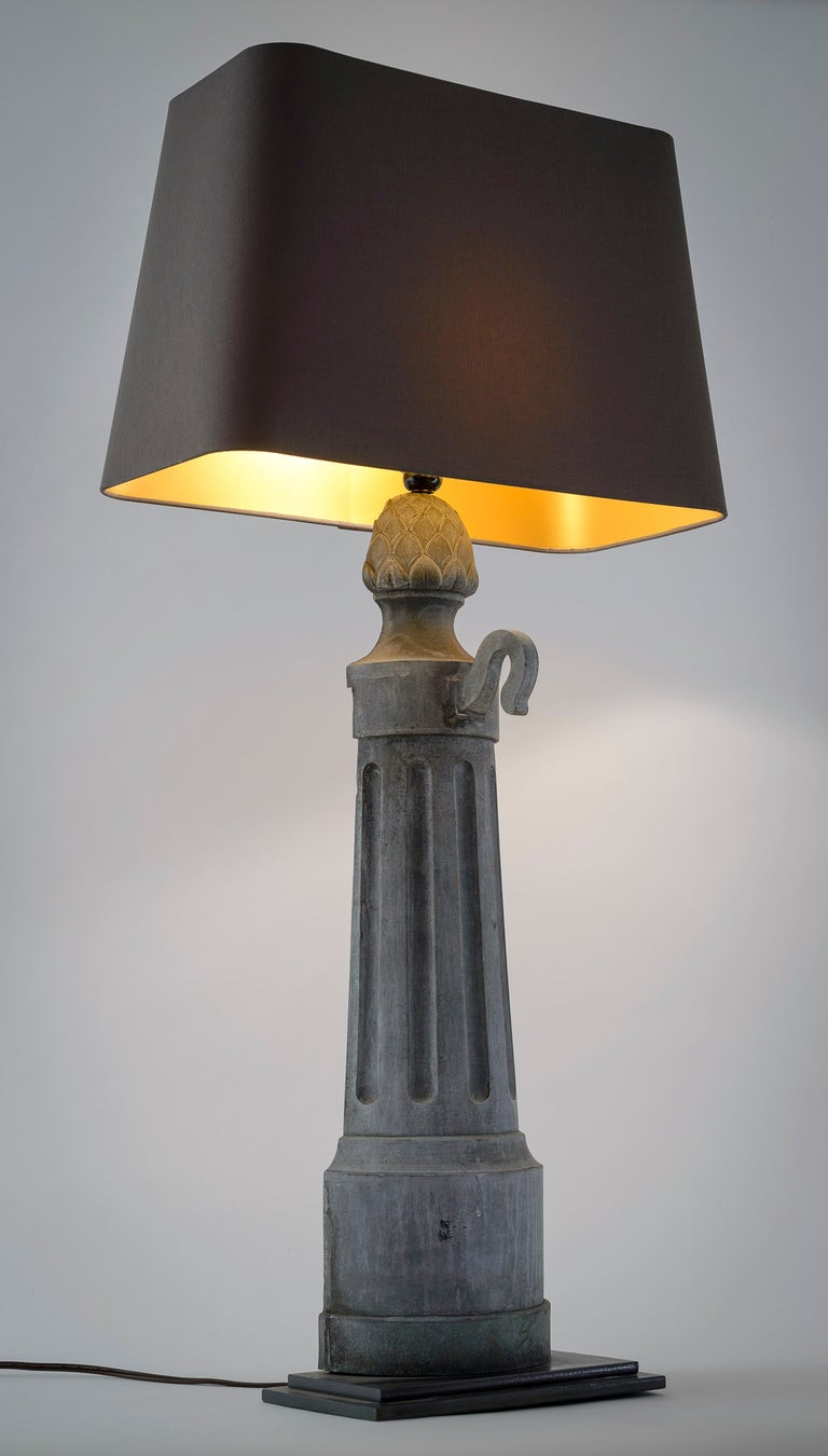 This pair of strikingly interesting lamps are repurposed metal object. The lamps are mounted on a simple two stage base. The gunmetal linen shades have a rich gold liner and a high low in-line switch. The lamps have been rewired for US use. When