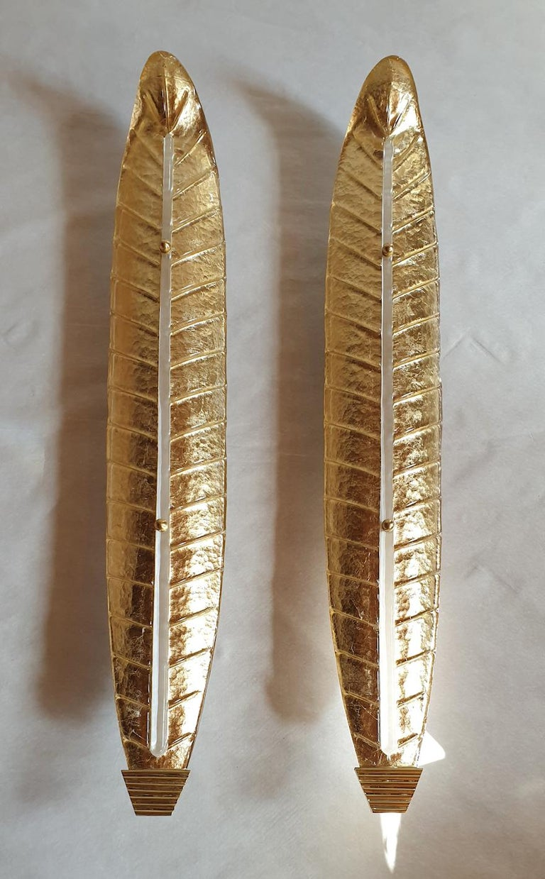 Pair of very tall and thin Mid-Century Modern Murano glass sconces, Barovier & Toso style, Italy 1970s. Made of brass mounts with a beautiful patina, and gold Murano glass leaves. The gold inside the sconces create a warm translucent light effect,