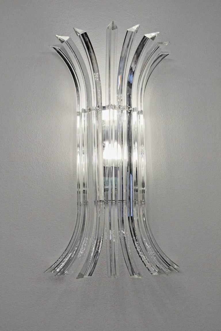 Elegant large pair of sconce to frame a wide mirror or a large entrance. Requires professional and skilled makers as the benting of the triedri was made keeping the crest out with a great play with light. Eight elements each. Tall. Very stylish and