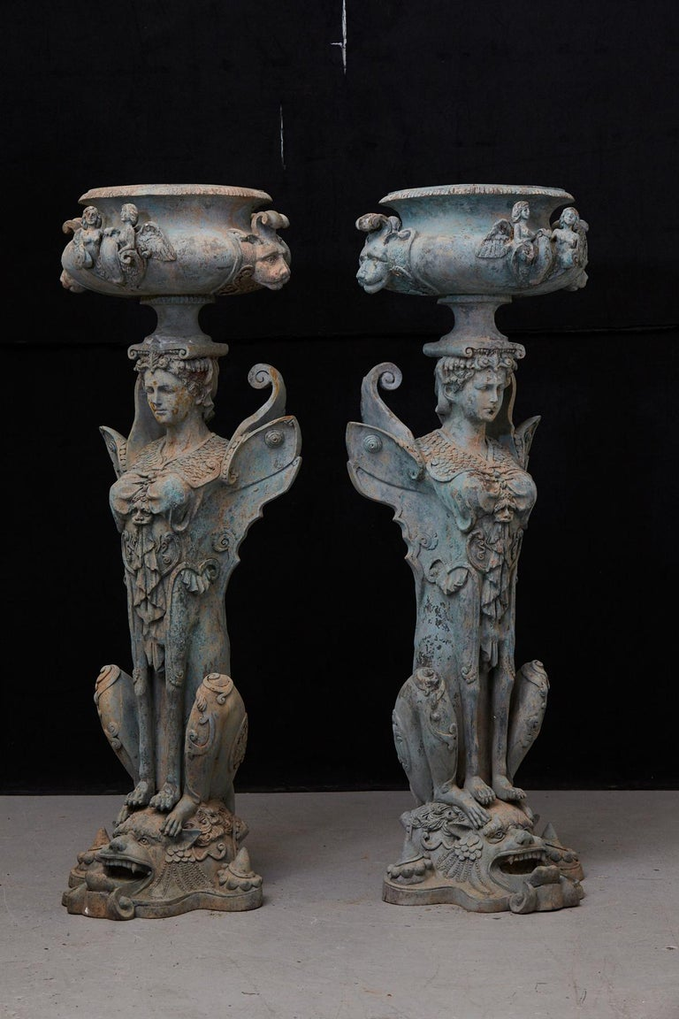 A pair of very rare and very tall (58 inches high) pair of patinated cast iron planters or urns, showing mythical creatures, chimeres, half-human, half-animal. Great details and patina. Diameter opening 13 inches.