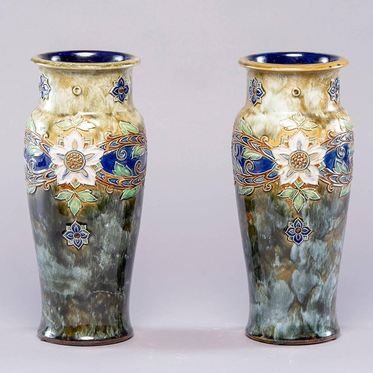 Pair of tall Royal Doulton Lambeth vase by Winnie Bowstead, circa 1920s. These large and striking pieces are decorated in the Art Nouveau style. The Royal Doulton impressed mark is on the underside of the base along with the and the incised initials