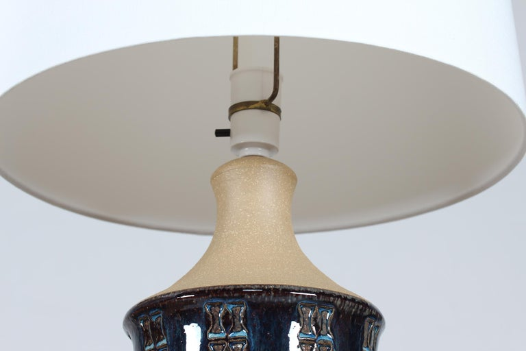 A pair of tall stoneware table lamps designed by Maria Philippi and made by the pottery Søholm on the island of Bornholm in Denmark in the 1960´s. The lamp base is decorated with an embossed pattern in bands and glossy glaze in blue colors - the