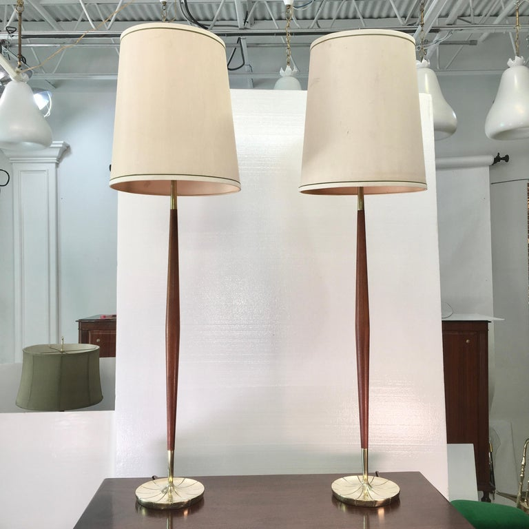 Handsome Mid-Century Modern pair of Stiffel lamps with elongated tapered walnut stems on brass finished cast aluminum petal form bases. These can be used either as petite floor lamps or extra tall table lamps. Each takes a single standard size