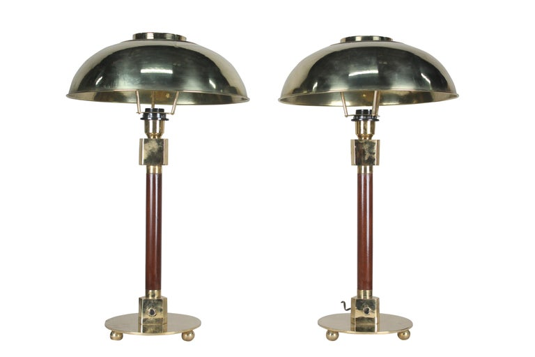 Pair of teak and brass table lamps from a ship's stateroom. Domed brass shade which lifts off and lamps are rewired for American use and takes one standard base light bulb, circa 1970s. Base diameter is 8