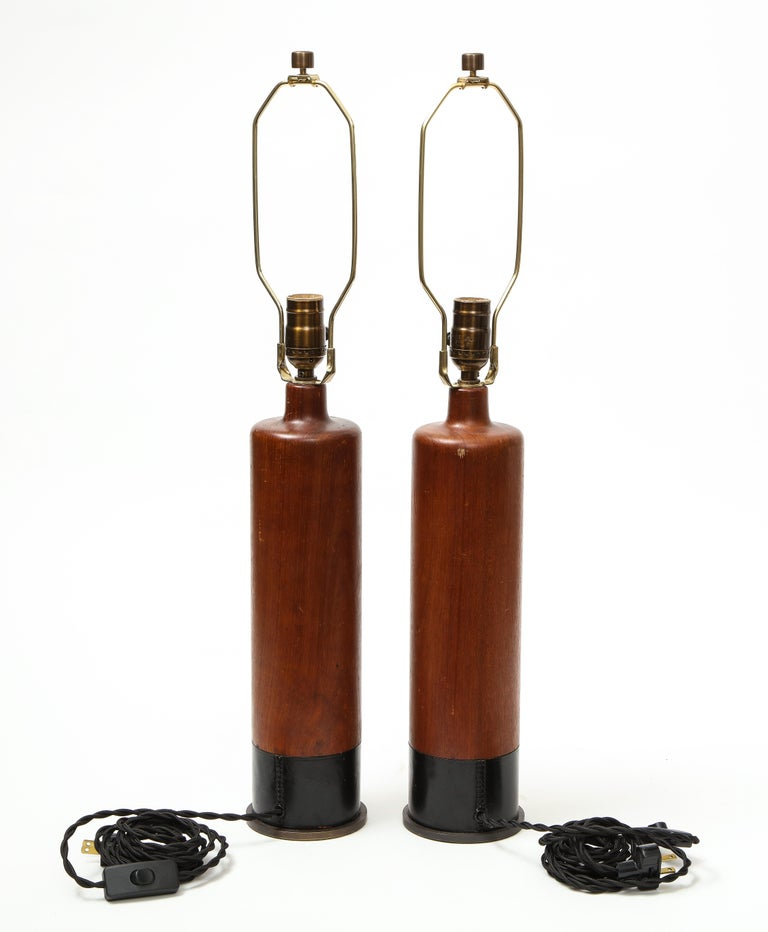 Pair of teak and leather table lamps, Denmark, circa 1970s.
