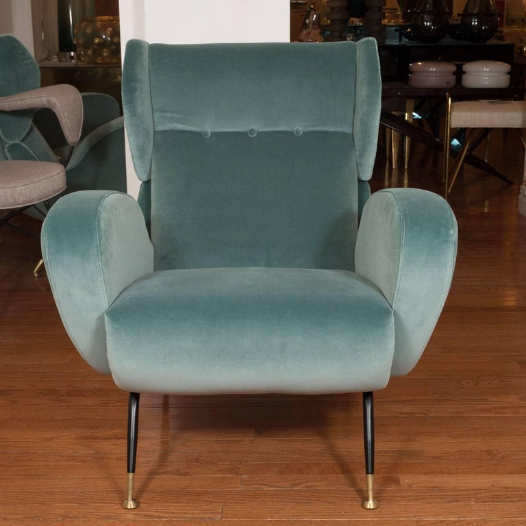 Pair of teal upholstered wingback armchairs with enameled metal legs and brass sabots.