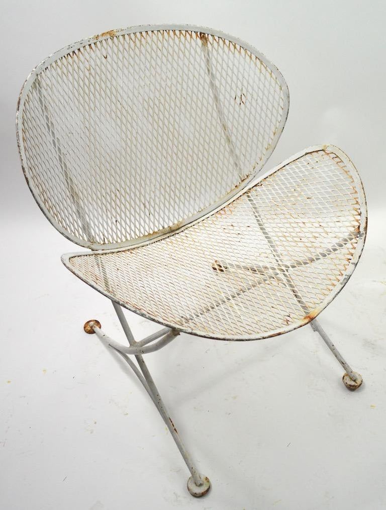 Pair of Clamshell chairs designed by Maurizio Tempestini for Salterini. Both chairs show significant cosmetic wear to the paint finish, both are structurally sound and free of repairs. Wrought iron rod frames with metal mesh seat and back. Designed