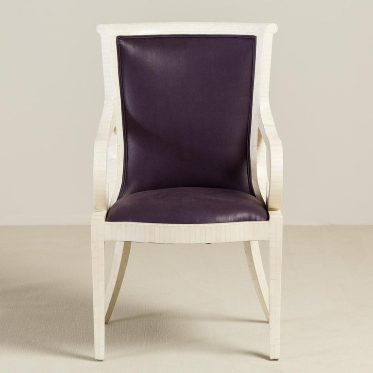 A pair of tessellated bone veneered carver dining chairs with scrolling arms and sabre legs and completed in a deep purple wax upholstery, designed by Enrique Garcel for Karl Springer, 1970s.  Karl Springer established a tiny workshop in Manhattan