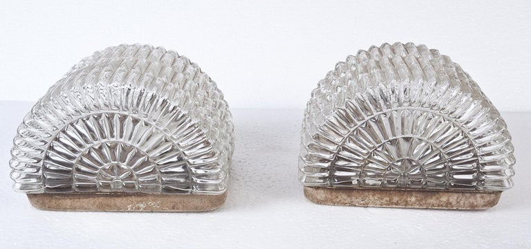 Pair of Mid-Century Modern textured glass sconce shades mounted on metal backs. Half round shape with a flat, textured top (or bottom depending upon how you decide to mount them). Takes an intermediate size European bulb which are readily available.