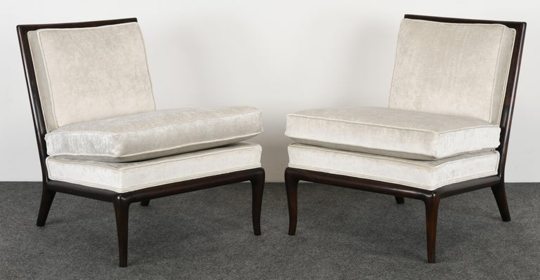 A luxurious pair of T.H. Robsjohn Gibbings slipper chairs for Widdicomb Furniture Company upholstered in Mokum Alabaster velvet fabric by Holly Hunt. The chairs are structurally sound and newly refinished wood.   Dimensions: 31.75