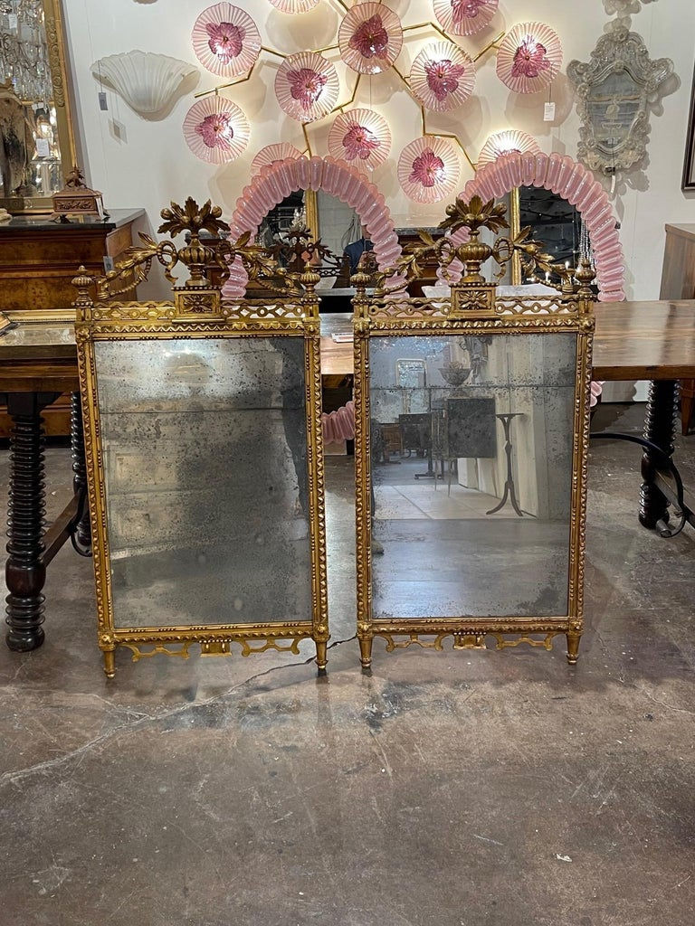 Gorgeous pair of the 19th century carved giltwood mirrors. Elaborate carvings of an urn with overflowing flowers. These mirrors are truly exceptional!