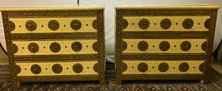 Three-Drawer Commodes, Chests or Nightstands in Hollywood Regency Style, a Pair  Pair of brass, natural stone and leather inlaid Moroccan off-white commodes, chests or nightstands. These exceptional chests depict and compliment the Hollywood Regency
