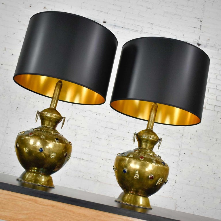 Stunning pair of hand hammered Tibetan brass lamps with glass jewels, etched and applied details, and new black Fenchel drum shades. Beautiful condition with wear as you would expect with vintage pieces. Very handmade, new wiring, and sockets with