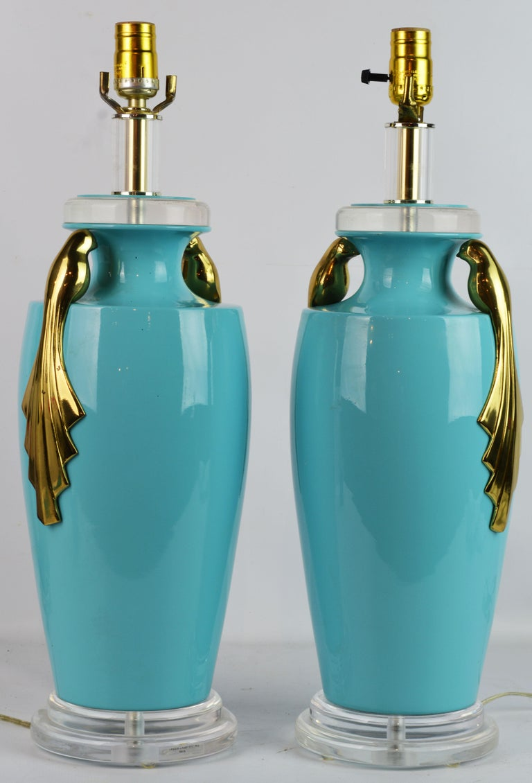 These Art Deco style table lamps by Bauer Lamp Company features Tiffany blue ceramic glazed bodies in the shape of Classic urns mounted with double stylized solid brass paradise birds. The lamps have Lucite bases and tops making the overall
