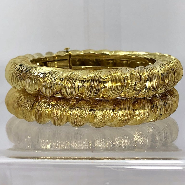 A matched pair of 18K yellow gold,  bangle bracelets by Tiffany &Co., featuring a twisted rope design. Can be worn individually or stacked  as shown. Hinged on one side. Signed Tiffany and Co. 18k. Fits a small wrist  size. Measuring 7/8 inch wide