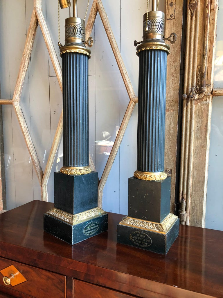 """A pair of fluted column-form table lamps circa 1800 of impressive size, in dark green painted tole with gilt bronze mounts, converted to electricity from fluid lamps, each marked with a metal label """"Lampe-Sylvant"""". From the personal collection of"""