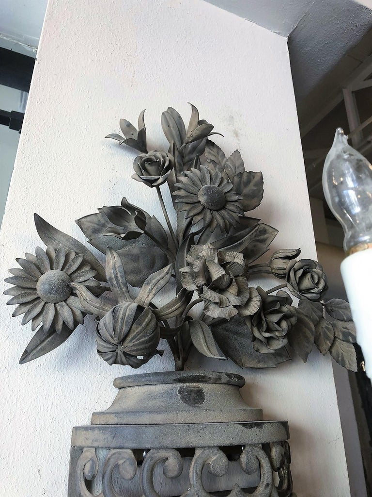 This pair of mixed metal outdoor wall sconces are adorned with flowers, acanthus leaves, and a cluster of grapes at the base.   Origin France,  circa 1940  Measurements: 25