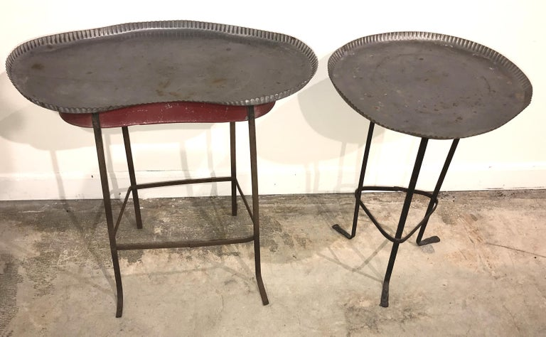 A great pair of tole gueridon metal side tables with crimped piecrust tops, one round and one kidney shaped, with forged metal bases with riveted stretchers. The kidney shaped table shows red paint on the skirt, which show some separation on its