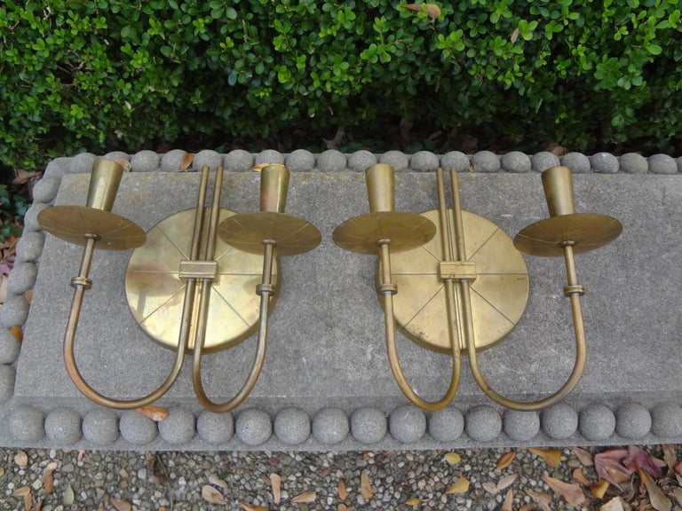 Fantastic pair of Mid-Century Modern brass sconces by Tommi Parzinger. These stunning modernist brass two-light sconces with geometric etched circular backplates were never electrified. Can be used with candles as originally designed or easily