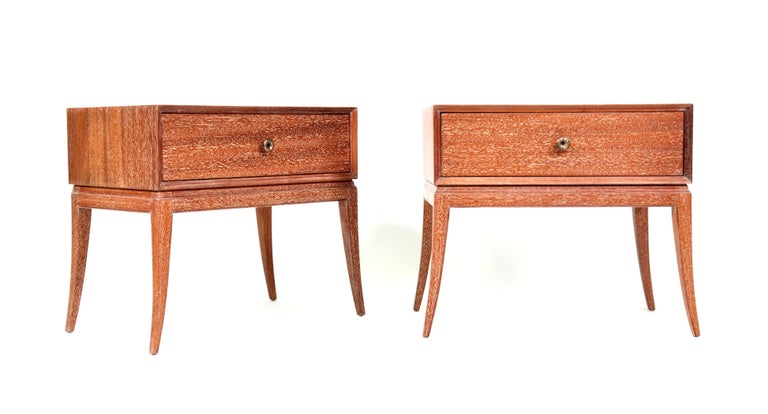 A gorgeous pair of Mid-Century Modern cerused mahogany and patinated brass bedside or end tables designed by Tommi Parzinger, and manufactured by Charak Modern. The nightstands are fitted with a drawer, the whole raised on elegant sabre legs. Each