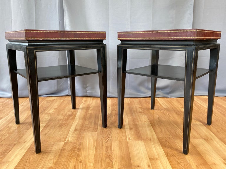 A pair of rare c. 1955 model 3303 occasional or end tables with leather top and ebonized mahogany frame by Tommi Parzinger for Charak Modern.  Exceptionally handsome Hollywood Regency design distinguished by a two-inch-tall leather-clad top with