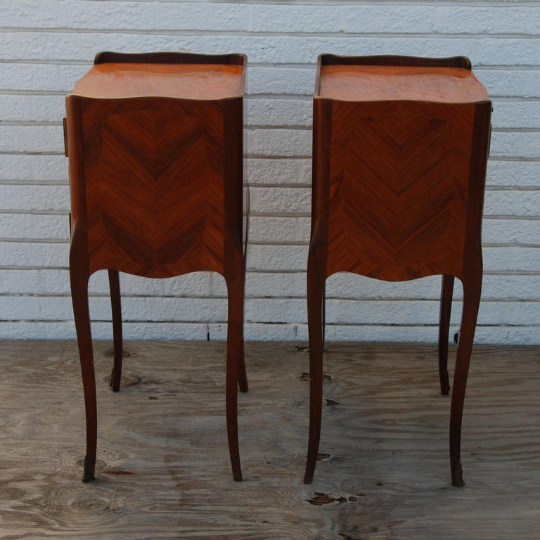 Pair of traditional mahogany nightstands with marquetry and Queen Anne legs  These nightstands feature marquetry inlay on front, with Queen Anne style