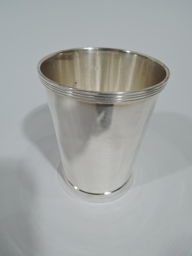 Pair of traditional sterling silver mint julep cups. Made by Fisher in Jersey City, New Jersey. Each: Straight and tapering sides, and reeded rim and foot. Fully marked and numbered 50. Total weight: 7 troy ounces.